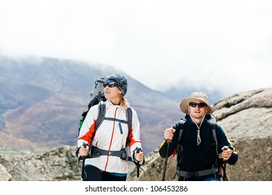 Couple hiking in mountains, Himalayas in Nepal. Man and woman trekking in summer nature outdoors. Young people traveling in Asia, trekkers on trail in wilderness.