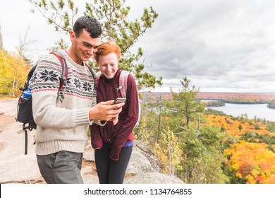 Couple hiking in Ontario during colorful fall season and checking smartphone or gps for map or photos. Travel and adventure concepts, caucasian man and woman models.