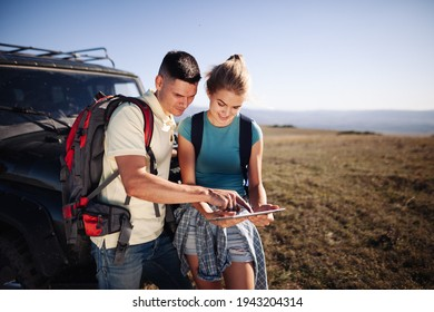 Couple hiking people using internet and tablet computer pc guide book