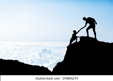 Couple hiking teamwork partners help each other silhouette in mountains, motivation and inspiration. Man and woman hiker helping hand trust on top of mountain climbing, beautiful sunset landscape.
