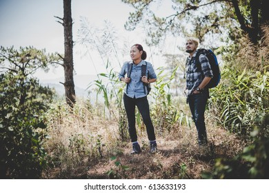 Couple hiking through forest to the mountaintop.