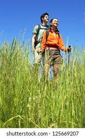 couple hiking together, blades of grass in the foreground, both wearing backpacks and holding hiking stick