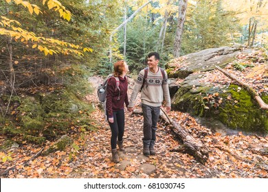 Couple hiking in the woods in Canada. Boy and girl walking with colourful trees all around and orange leaves on the ground during the fall season. Autumn and nature concepts.