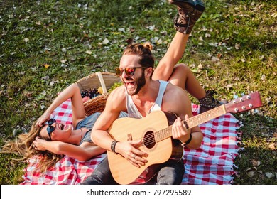 Couple of hipsters laughing on a picnic while man is holding a guitar