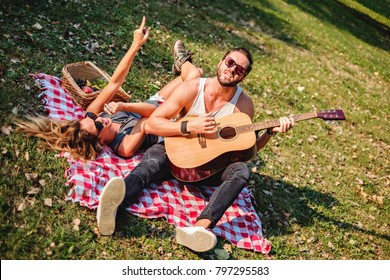 Couple of hipsters singing and dancing in a park