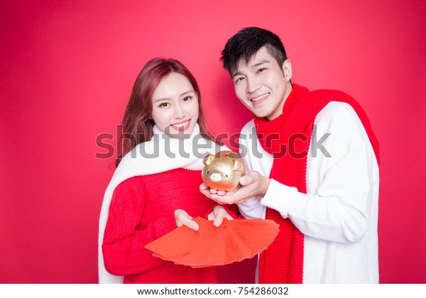 couple hold pig and envelope on the red background