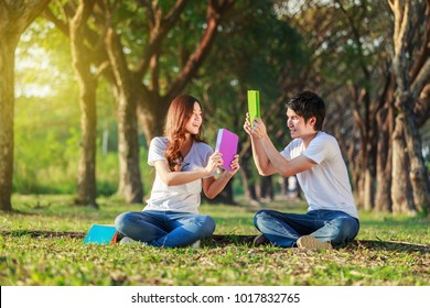 couple holding a book and resting in the park