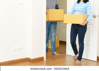 Couple holding boxes into their home - moving house concept.