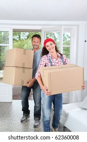 Couple holding boxes in their new home