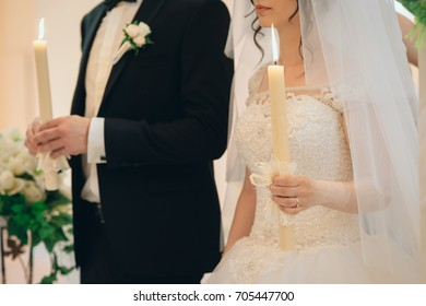 couple holding candles during the church wedding ceremony