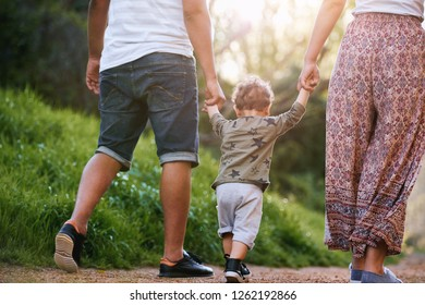Couple holding child's hand helping him walk, carefree childhood