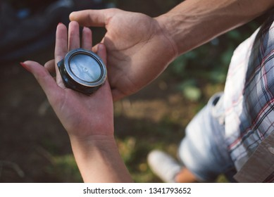 Couple holding a compass outdoors in the nature