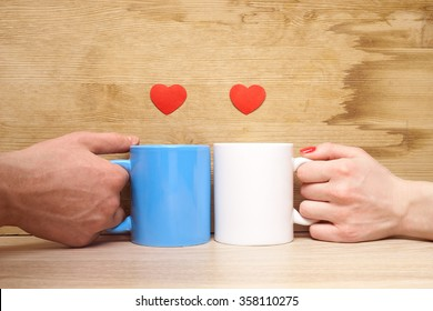 couple holding a cup with hearts