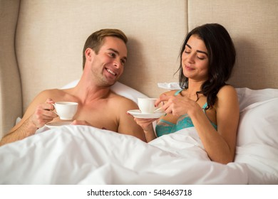 Couple holding cups in bed. Young man smiling. You keep surprising me.