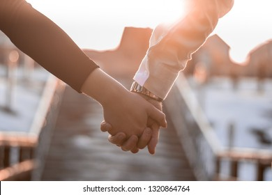 couple holding eitchother hands in the sunset