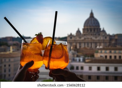 A couple is holding glasses of Aperol in the bar inside the Castle Sant'Angelo. Glasses of Aperol and St Peter's basilica at the background. Concept photo of traveling to Italy.