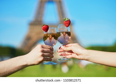 Couple holding glasses with pink wine and strawberries in front of the Eiffel tower in Paris, France