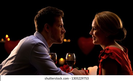 Couple holding hands and admiring each other on romantic date in restaurant