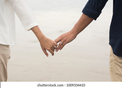 A couple holding hands at beach.