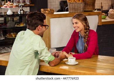 Couple holding hands in the cafeteria