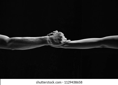 Couple holding hands in the dance. Male and female hands close-up on a black background. Minimalism, geometry, line. BW.