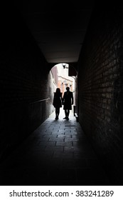 Couple holding hands in dark London alley street grimey
