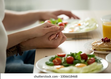 Couple holding hands enjoying delicious homemade meal together, man and woman have pancakes, eggs with salad on tasty organic vegetarian breakfast, healthy food on dining table for two, close up view