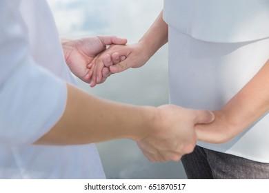 Couple holding hands in garden