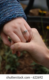 couple holding hands - girl w/ engagement ring