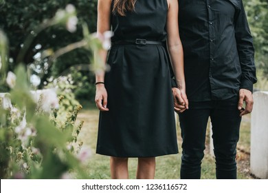 Couple holding hands at a graveyard