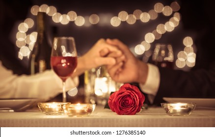 Couple holding hands having a romantic dinner date, Valentines day, anniversary concepts.