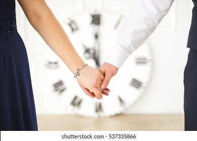 couple holding hands on the background of the big clock