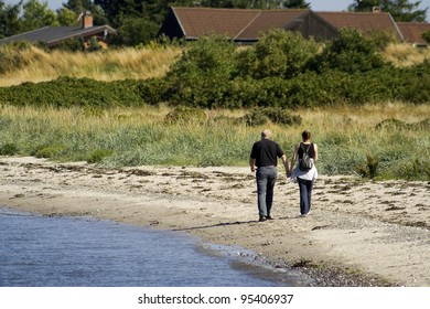 Couple holding hands on a Danish beach