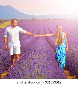 couple holding hands on lavender fields at sunset in Provence, France