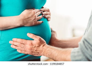 Couple holding hands on pregnant belly