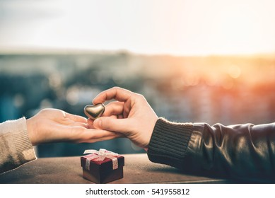 Couple holding hands on the rooftop with small red gift box in foreground