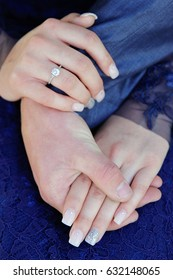 Couple holding hands on woman's lap with girl wearing blue lace dress and her hand on top of his arm closeup