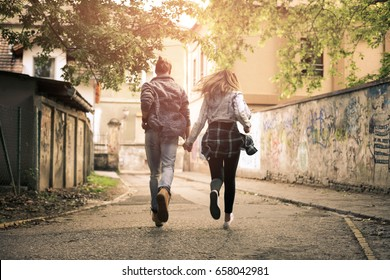 Couple holding hands outdoors. Young couple running trough  street.