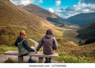 Couple holding hands and overlooking view of Scottish mountains during sunset in Autumn on the Isle of Skye, Scotland, UK.