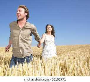 Couple holding hands and running in wheat field