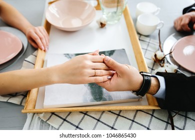 Couple holding hands sitting at table