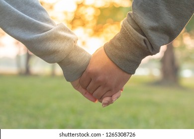 Couple holding hands at sunset. Romantic young couple in love.