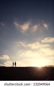 Couple Holding Hands at Sunset Silhouette