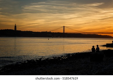 Couple holding hands at sunset sitting on the banks of Tagus river in Lisbon with Ponte 25 de Abril and National Sanctuary of Christ the King in the background.