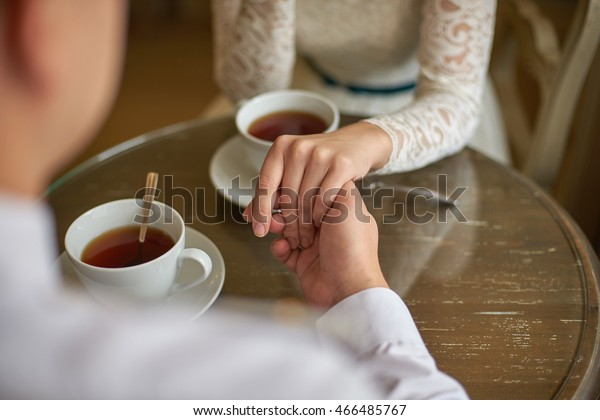 couple holding hands at the table in a cafe for a cup of tea