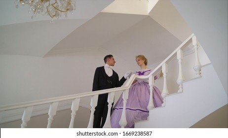 Couple holding hands while climbing stairs. A young couple in suits that were worn in the 19th century climb the stairs. A guy and a girl in karty outfits climb the stairs. 19th century clothes on a