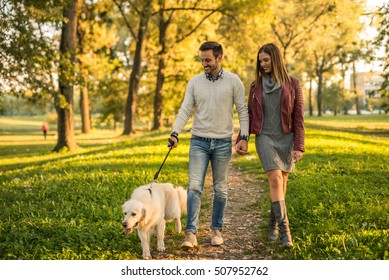 Couple holding hands while walking a dog in the park.