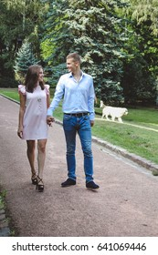 Couple holding hands while walking in park. Girl dressed in pink dress and man in blue shirt and jeans