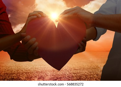 Couple holding a heart against sunrise over field