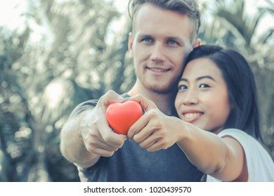 Couple holding a heart, the idea of planning a wedding.